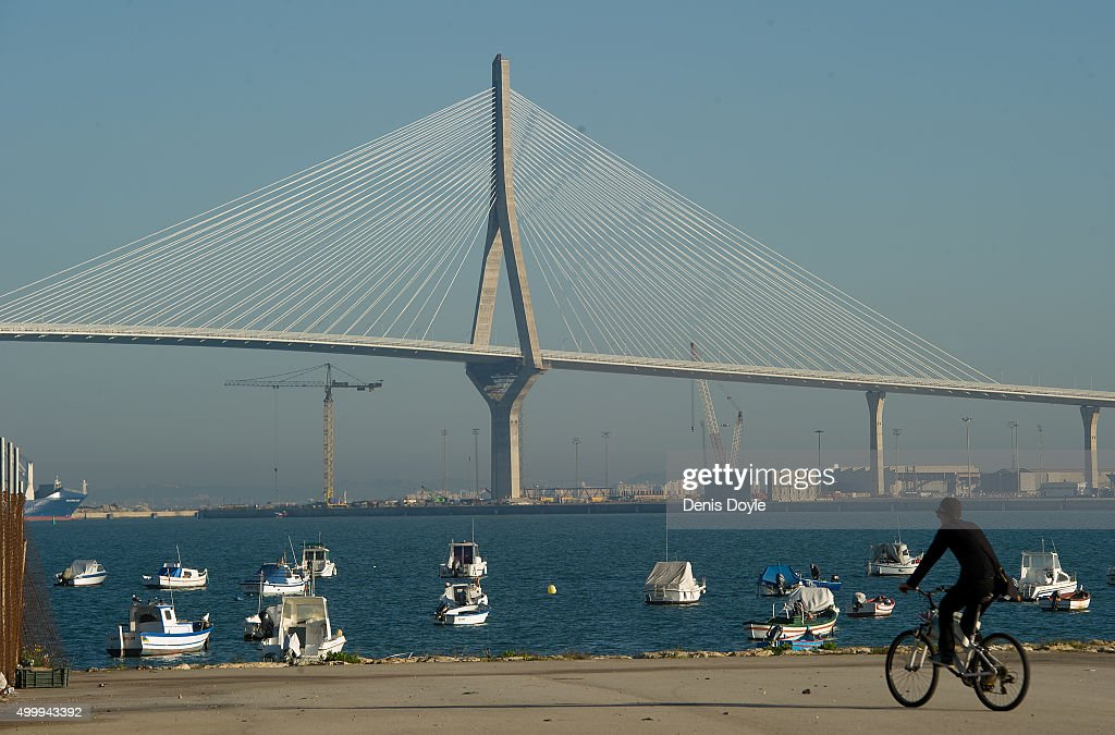 A fisherman cycles towards his boat with the landmark 1812 Consttiution Bridge in the background on December 3 2015 in Cadiz Spain The bridge has a...