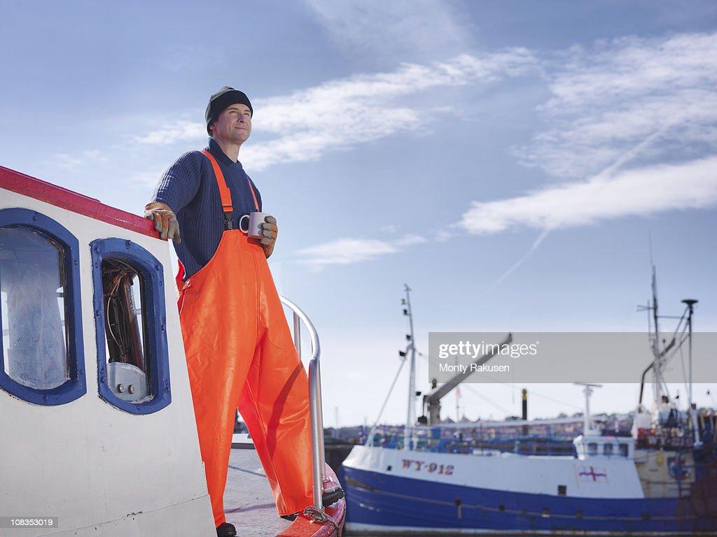 Fisherman drinking tea on boat