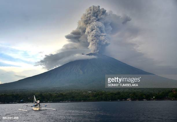 TOPSHOT A fisherman drives a traditional boat as Mount Agung erupts seen from Kubu subdistrict in Karangasem Regency on Indonesia's resort island of...