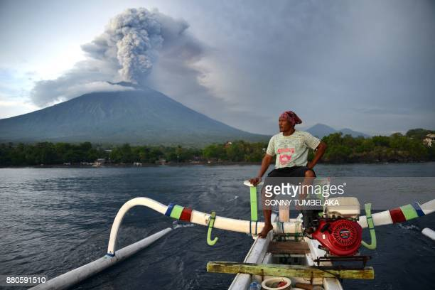A fisherman drives a traditional boat as Mount Agung erupts seen from Kubu subdistrict in Karangasem Regency on Indonesia's resort island of Bali on...