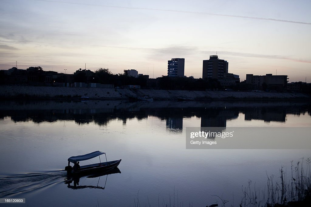 A fisherman drives his motorboat on the Tigris river at dawn on March 29 2013 in Baghdad Iraq Ten years after the regime of Saddam Hussein was...