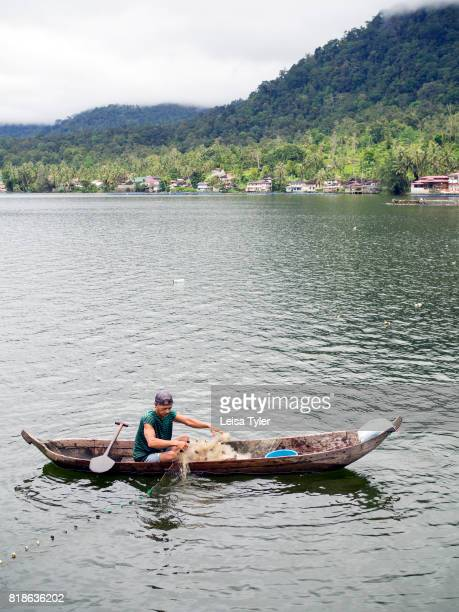 MANINJAU BUKITTINGGI SUMATRA INDONESIA A fisherman fishing from his boat on the shores of at Lake Maninjau a volcanic crater lake in West Sumatra...
