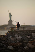Fisherman fishing in front of Statue of Liberty