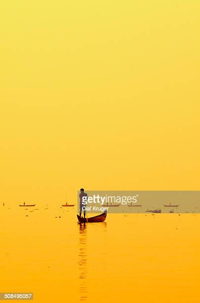 Fisherman fishing on Lake Vembanad at sunrise, Kerala, southern India, India, Asia