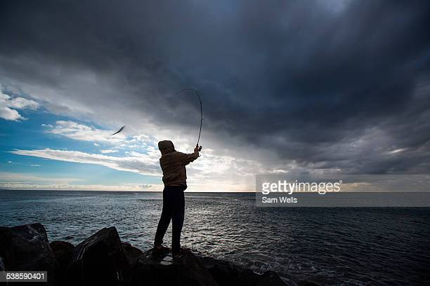 Fisherman fishing while storm blows in