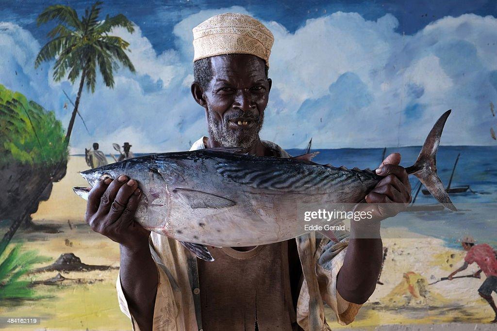 A fisherman holding a Tuna fish in The island of Zanzibar Tanzania Africa