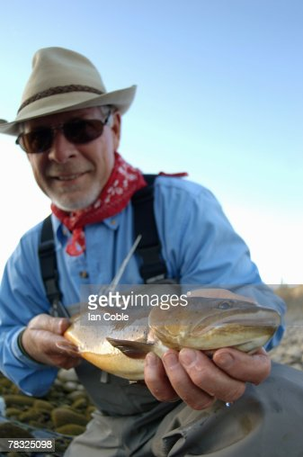 Fisherman holding fish : Stock Photo