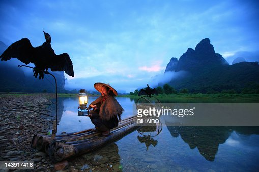 Fisherman holding flashlight and two crows