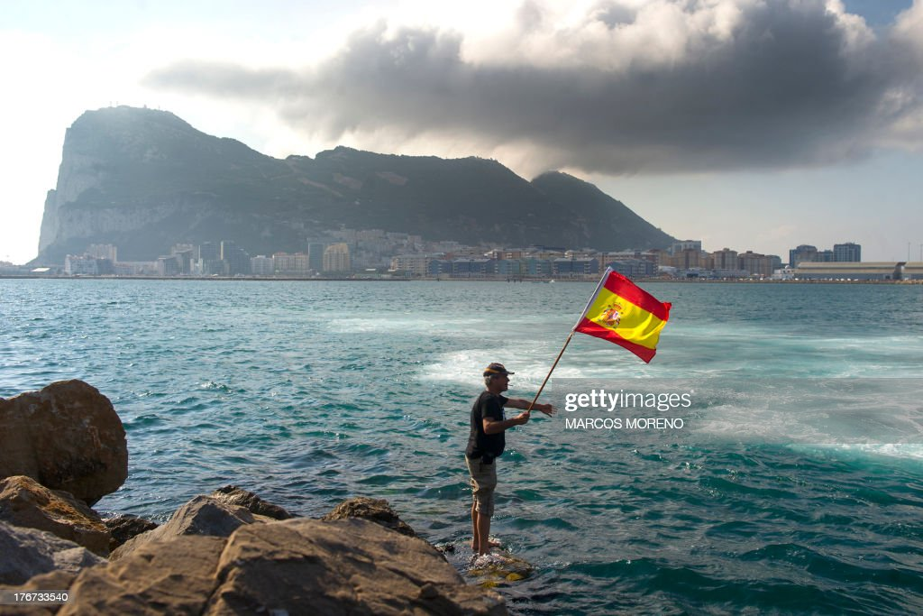 A fisherman holds a Spanish flag during a protest in the bay of Algeciras, near the Rock of Gibraltar, on August 18, 2013. A Spanish protest fleet of 38 fishing boats sailed towards Gibraltar today to demand the British outpost remove 70 concrete blocks it has dropped in their fishing grounds. British naval and Gibraltar police patrols blocked the Spanish boats from entering disputed waters around the concrete reef, which has sparked an angry row between London and Madrid.
