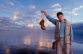 Fisherman holds an old boot