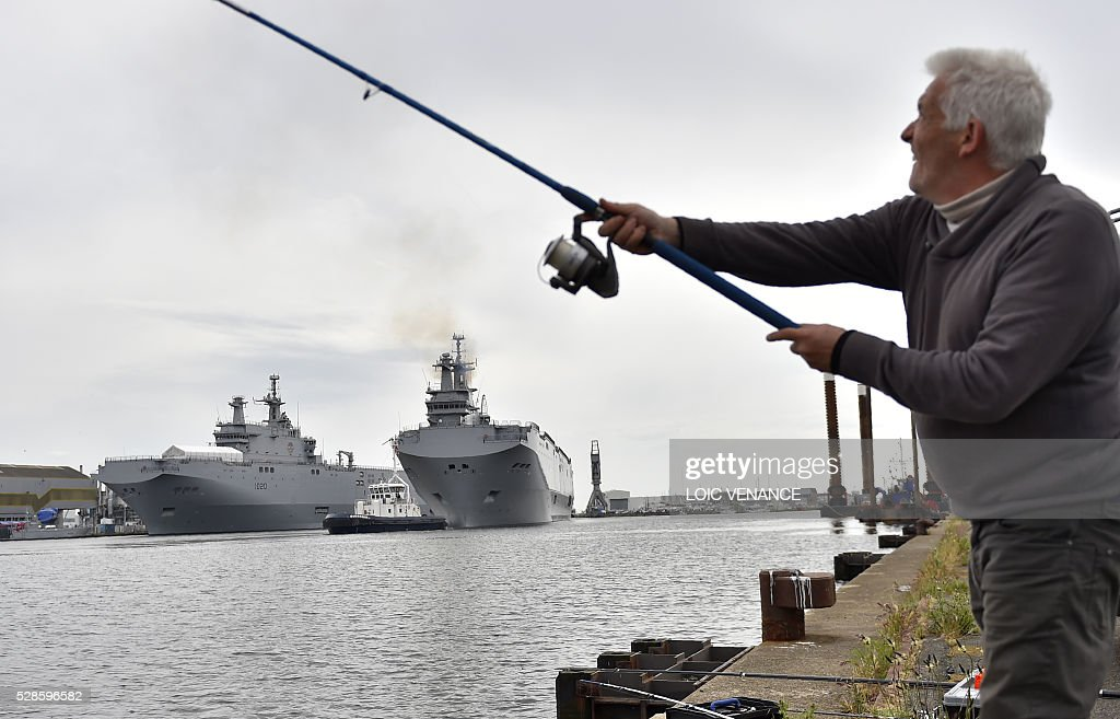 A fisherman holds his rod as the Gamal Abdl Nasser (ex-Vladivostok) Mistral class ship leaves the harbour for a one week training session on May 6, 2016 in Saint-Nazaire, western France. The 'Nasser', first one of the two Mistral class ships sold by France to Egypt after its first sale cancellation to Russia, leaves Saint-Nazaire (Loire-Atlantique) on Friday for a week of Egyptian crew training at sea. / AFP / LOIC