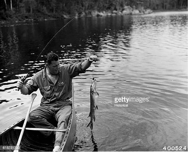 A fisherman in a canoe has caught a large northern pike in Lac Le Croix Superior National Forest Minnesota July 30 1940 | Location Lac Le Croix...