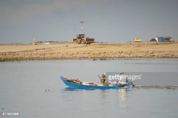 A fisherman in front of the land reclamation island D' The island is a part of government's National Capital Integrated Coastal Development plan...