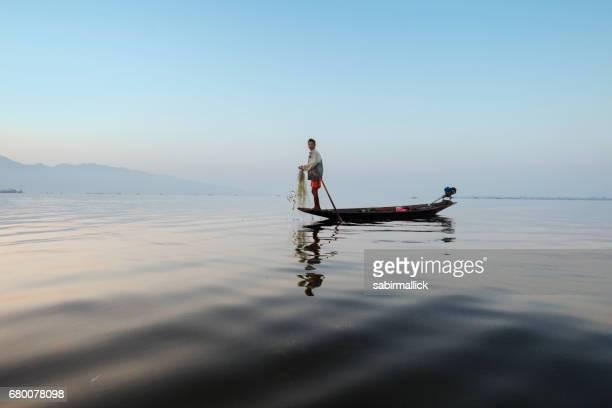 Fisherman in wooden boat, Myanmar