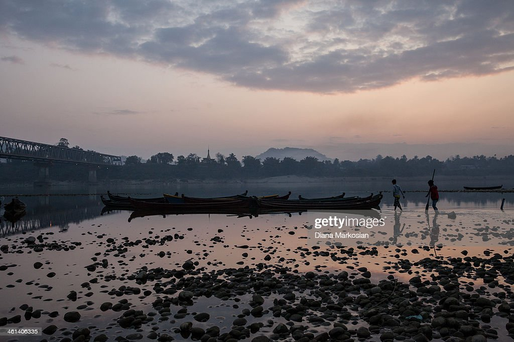 A fisherman is seen at sunset on Irrawaddy River on December 29, 2013 in Kachin State, Myanmar. The Irrawaddy River is the lifeline of Burma, running through the center of the country. The River provides vital nutrients to wetlands and floodplain areas downstream, including the delta region which provides nearly 60 percent of Burma's rice. A massive Chinese hydropower project is under construction in the Irrawaddy river, despite fierce opposition from the Kachin Independence Organization, which broke a 17-year-ceasefire after warning that it would fight to block the project. In 2011, the hydroelectric dam project was suspended under the mandate of President U Thein Sein. The project, which involves building a 152-meter-tall hydroelectric dam at the confluence of the two rivers that form the Irrawaddy, is the brainchild of a giant Chinese state-owned firm, China Power International.