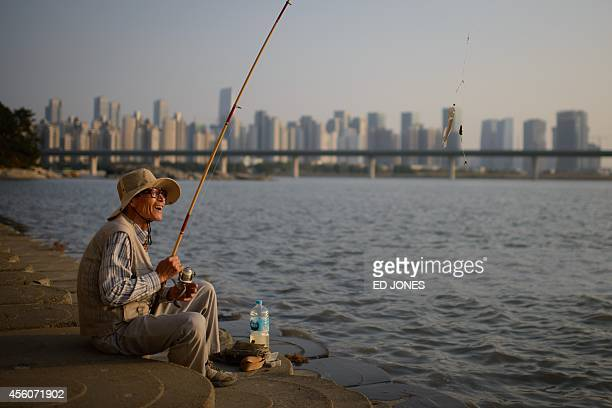 A fisherman laughs as he reels in a catch before the skyline of the Songdo area of Incheon on September 25 2014 Incheon is hosting the 2014 Asian...