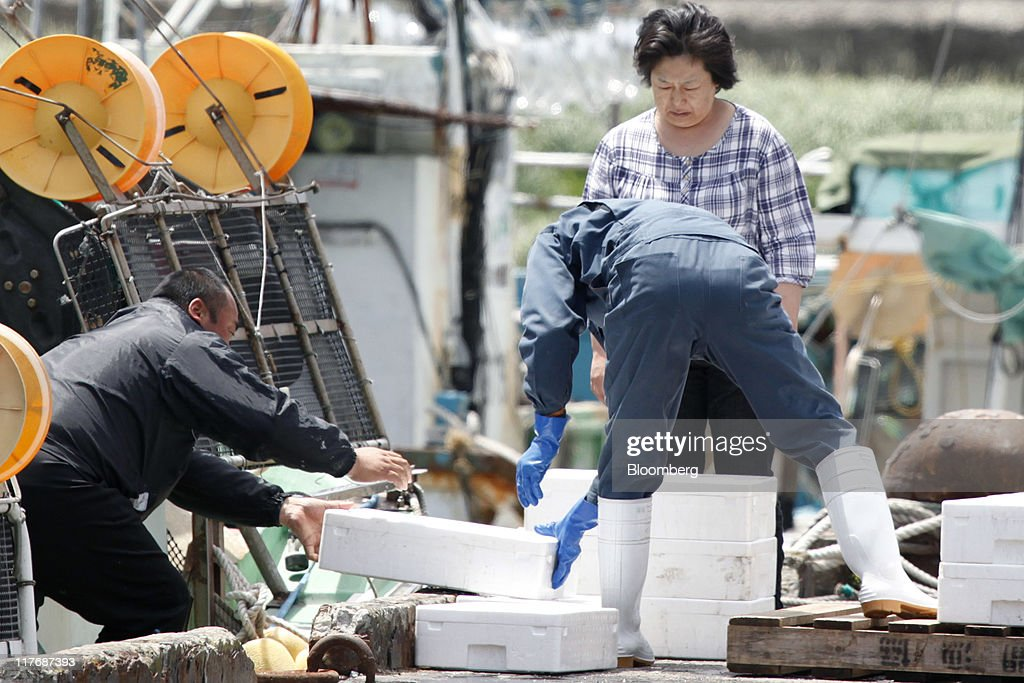 A fisherman, left, unloads boxes containing fish from a boat at a fishing port in Oma Town, Aomori Prefecture, Japan, on Sunday, June 26, 2011. Over the 29 years since Electric Power Development Co.'s (J-Power) nuclear plant was proposed, Oma has received almost 11 billion yen in subsidies, said Kenichi Ito, a town planning official. In Oma and other Aomori towns, the grants helped offset declining revenues that threatened the survival of rural communities, officials said. Photographer: Kiyoshi Ota/Bloomberg via Getty Images
