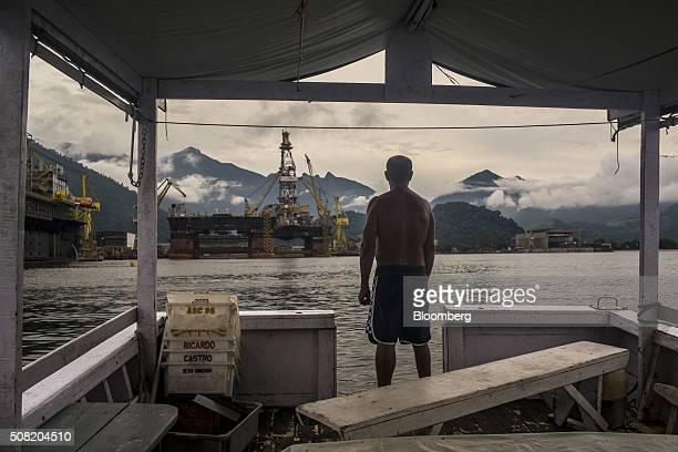 A fisherman looks toward a Petroleo Brasileiro SA Floating Production Storage and Offloading vessel at a maintenance shipyard in Angra dos Reis...
