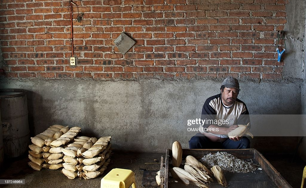 A fisherman makes 'white charales' tamales in a small building near the shore of the Cuitzeo lagoon on January 10 2012 in Michoacan state Mexico The...