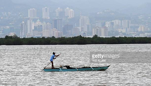 A fisherman manueovers his wooden boat as he fishes along the shoreline of Cordova town Cebu provnce in central Philippines on January 20 2014 AFP...
