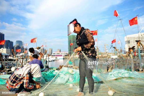 A fisherman mends fishing nets at a fishing port on August 30 2017 in Qingdao Shandong Province of China Fishing ban started from May 1 on China's...