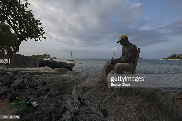 A fisherman mends his net in Ile Vache Haiti on Jul 19 2015 Boston Adult Technical Academy teacher Nate Eckstrom spent a month in Haiti to learn the...