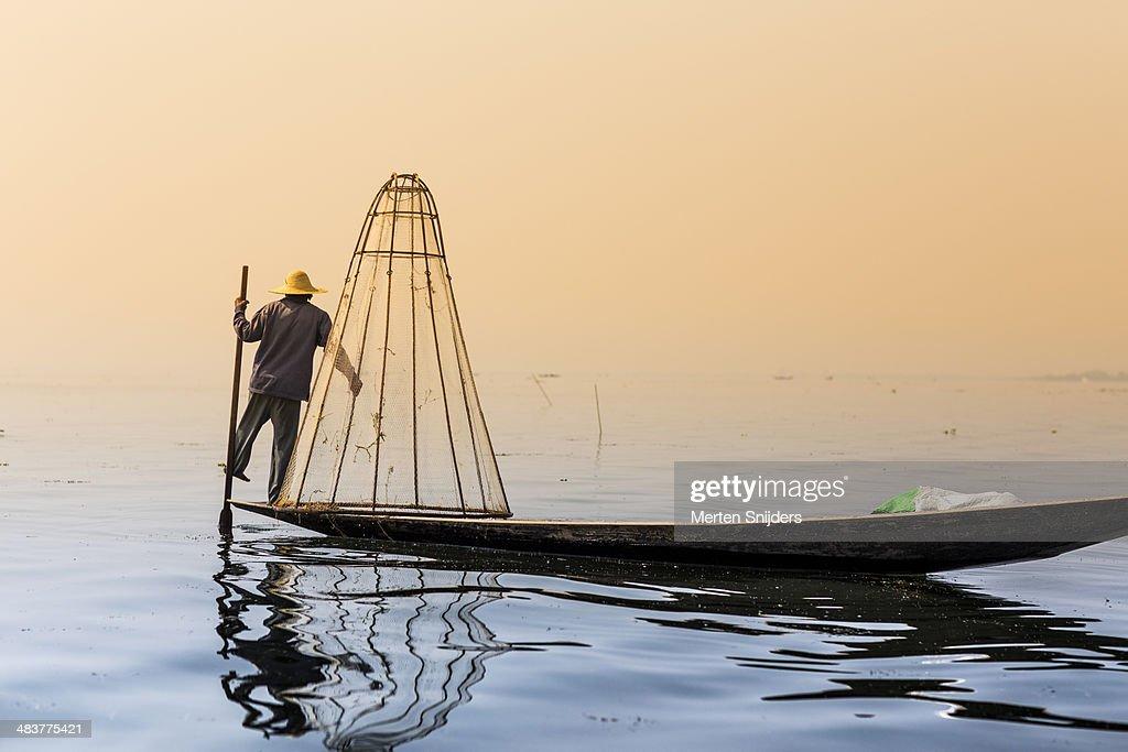 Fisherman observing lake from canoe