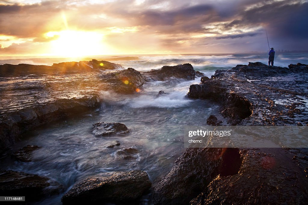 A fisherman on a rocky outcrop on the seashore at sunrise : Stock Photo