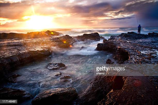 A fisherman on a rocky outcrop on the seashore at sunrise