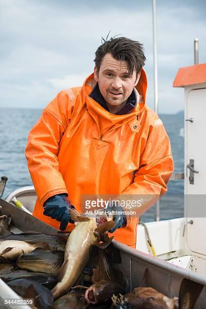 Fisherman on boat holding fish