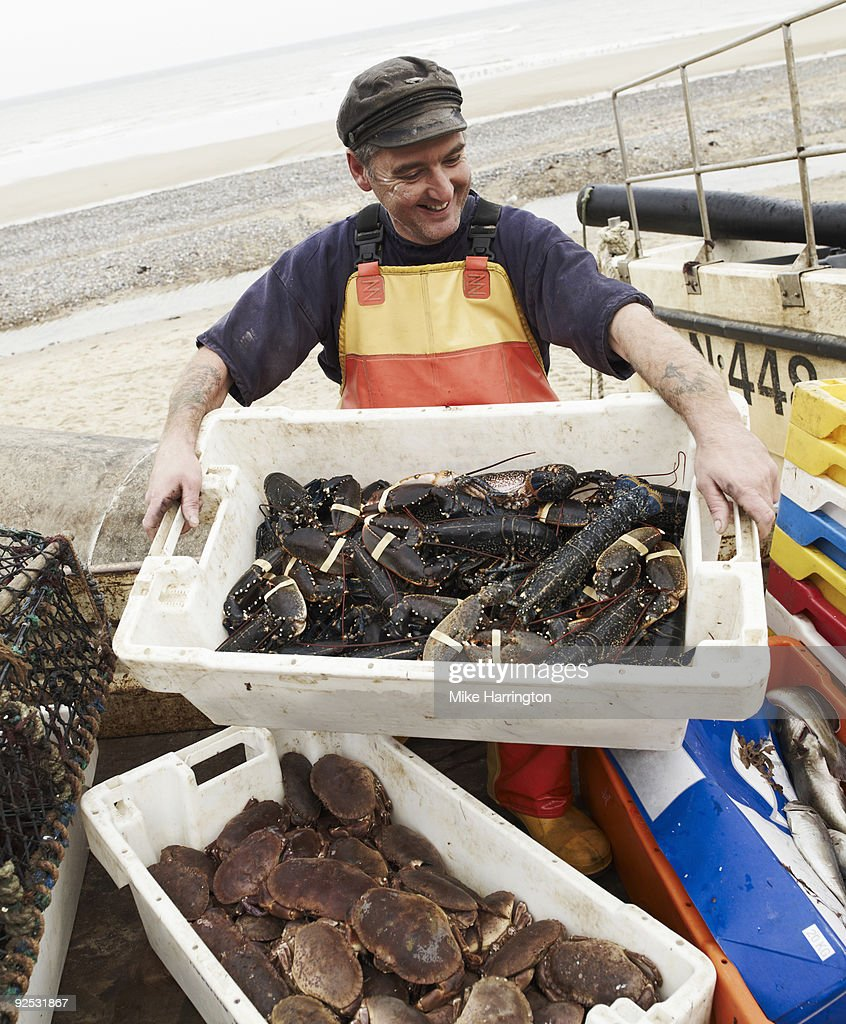 Fisherman on Cromer beach with his catch  : Stock Photo