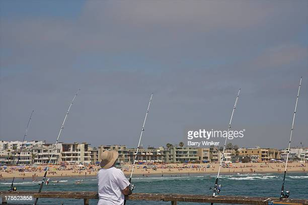 Fisherman on pier with multiple rods