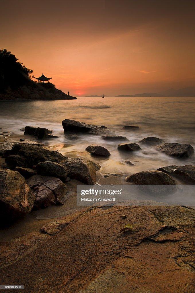 Fisherman on rocks at sunset