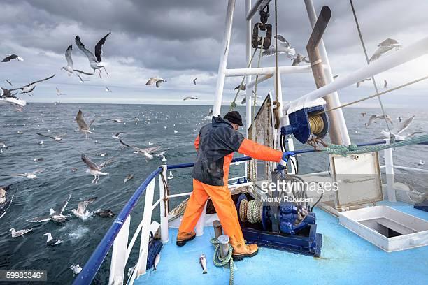 Fisherman operating winch on deck of trawler