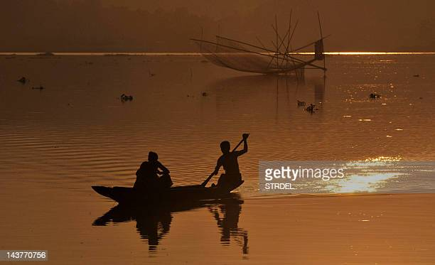 A fisherman paddles his boat after checking his fishing net at the Brahmaputra river near Panikhati village on the outskirts of Guwahati city on...