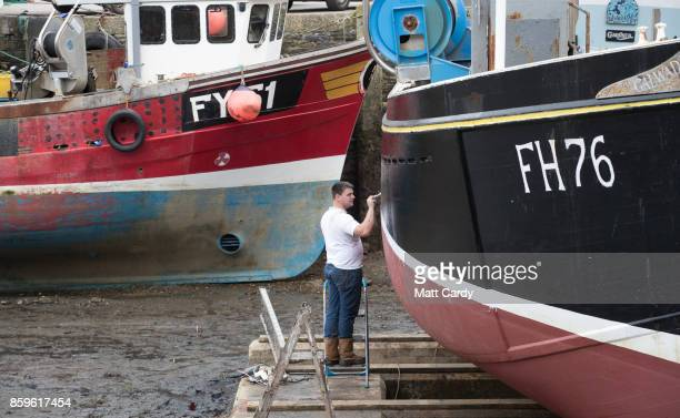 A fisherman paints a boat in the harbour in the village of Mevagissey which has submitted plans to limit the number of second homes on October 9 2017...