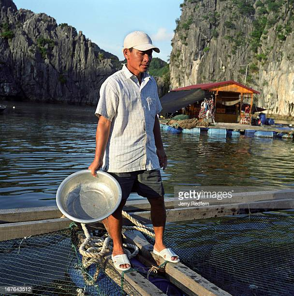A fisherman pauses after feeding the huge catfish growing in a pen beneath his family's floating home near Cat Ba Island in Halong Bay The captive...