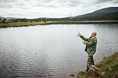 Fisherman catching fish in river at springtime