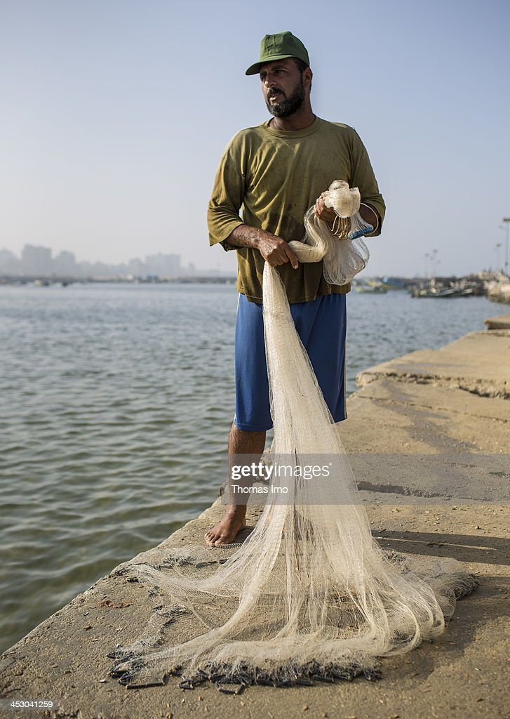 A fisherman pictured straightening out his net at the harbor on November 06, 2013 in Gaza City, The Palestinian Territories.