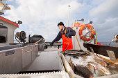 Fisherman pilling up fishing line on fishing boat