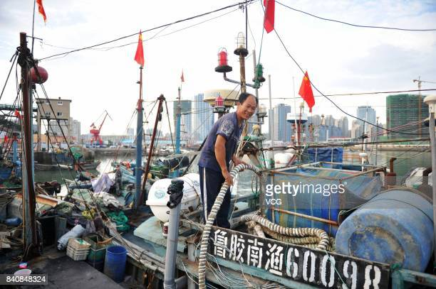 A fisherman prepares fishing gears at a fishing port on August 30 2017 in Qingdao Shandong Province of China Fishing ban started from May 1 on...