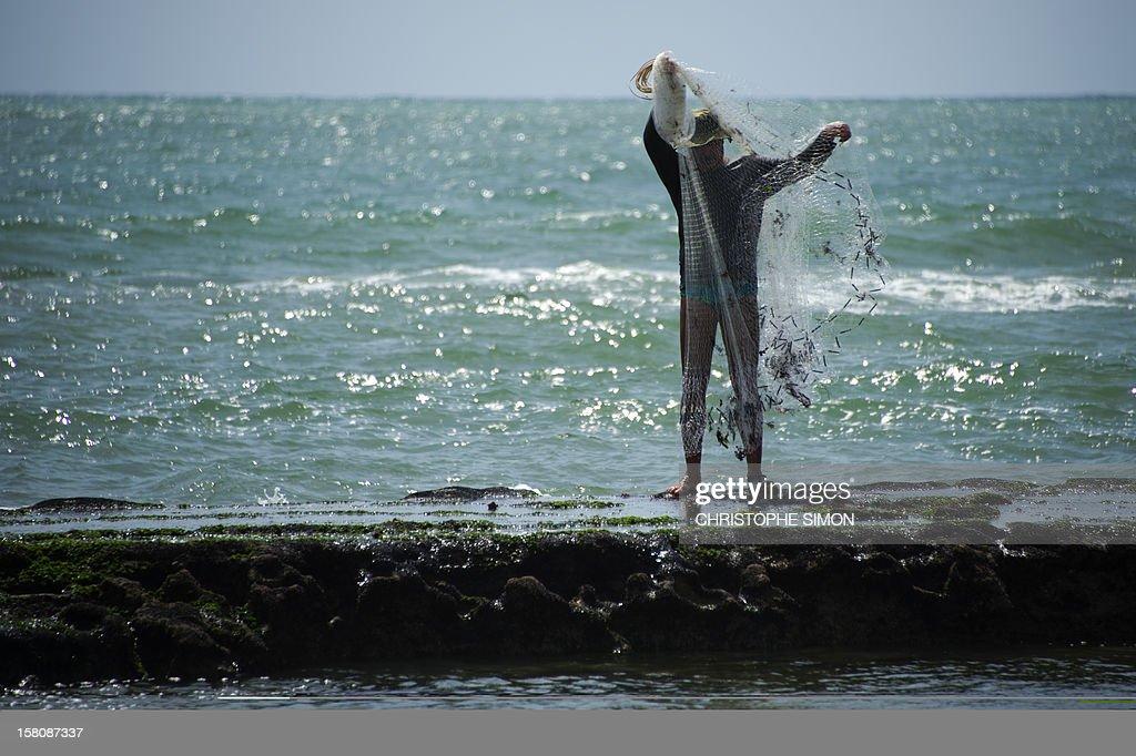 A fisherman prepares his net, in Recife, state of Pernambuco, Brazil, on December 09, 2012.