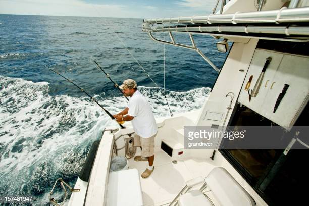 Fisherman Prepping Fishing Rods on Private Boat in Ocean