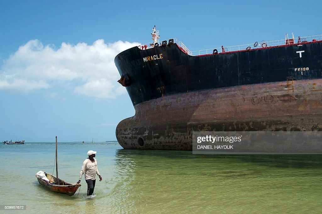 A fisherman pulls a canoe as he walks by the Marshall Islands flagged tanker vessel 'Miracle' after it ran aground at the mouth of the Dar es Salaam's harbour on February 13, 2016. / AFP / DANIEL HAYDUK