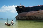 A fisherman pulls a canoe as he walks by the Marshall Islands flagged tanker vessel 'Miracle' after it ran aground at the mouth of the Dar es...