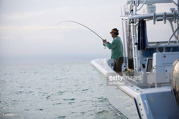 A fisherman reels in a catch off the side of his boat.