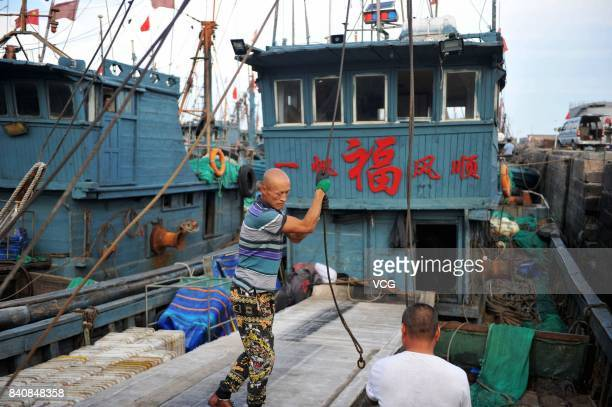 A fisherman repairs vessels at a fishing port on August 30 2017 in Qingdao Shandong Province of China Fishing ban started from May 1 on China's...
