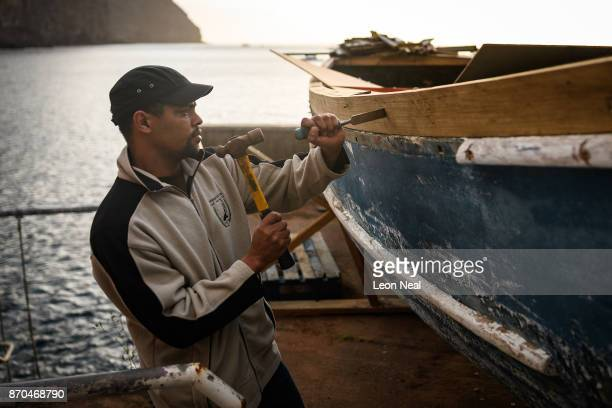 Fisherman Robin Stander continues renovation work on the boat 'Tina' on October 23 2017 in Jamestown Saint Helena The waters around the island...