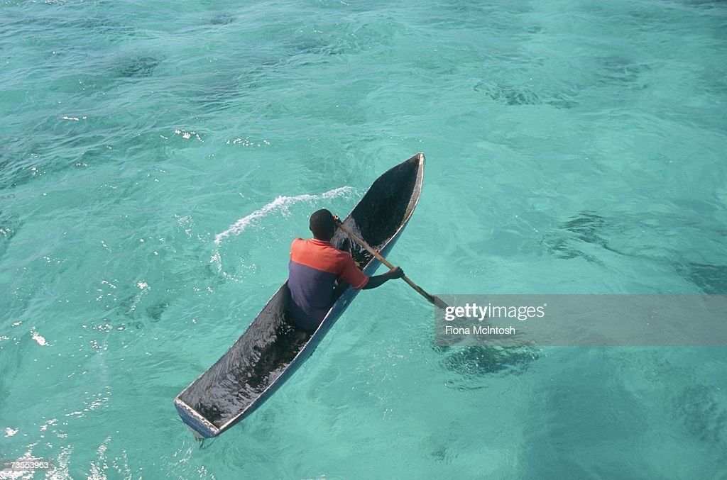 Fisherman Rowing in a Dugout Canoe