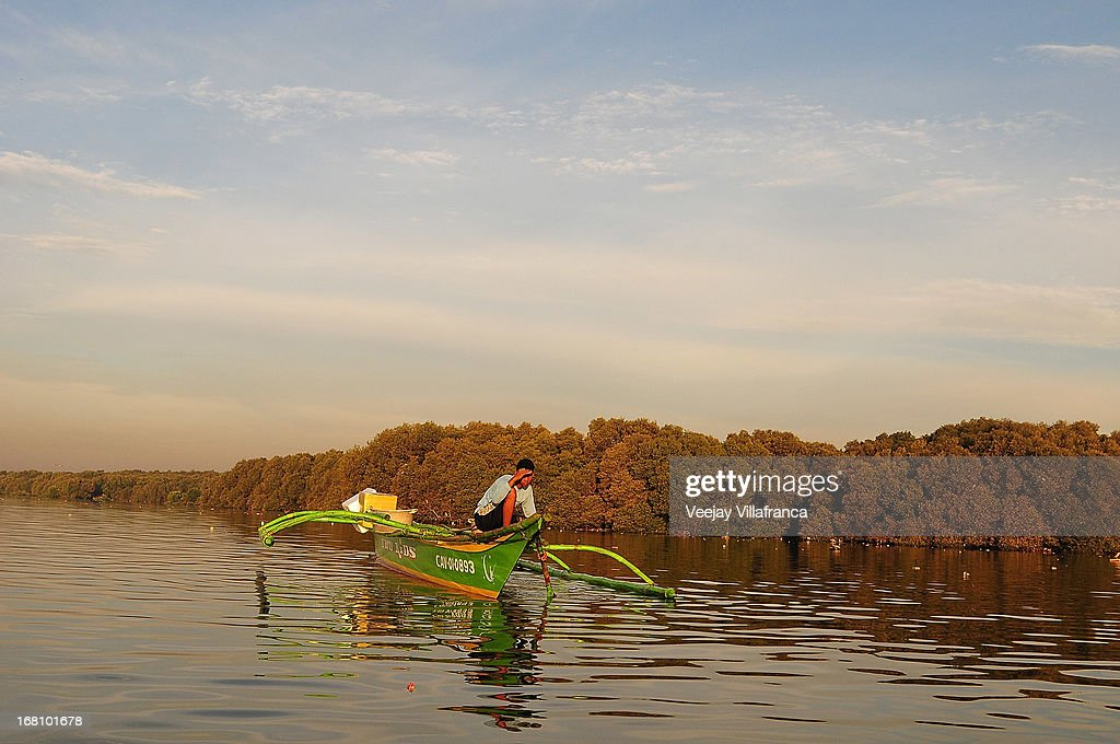 A fisherman rows his boat near Freedom Island on May 5, 2013 in Manila, Philippines. Around 13,000 hectares of the coastal area is to be recalimed and developed under the Public Private Partnership (PPP) of the Philippine government.